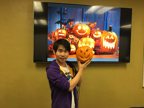 Cong Qu poses with a jack-o-lantern.